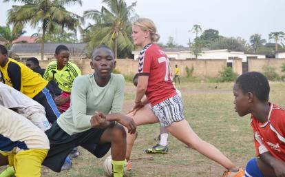 ガーナでサッカー指導にあたるボランティアと地元の少年たち